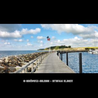 Steg an der Grömitzer Hafenmole mit Fahnen und Blick auf die Steilküste